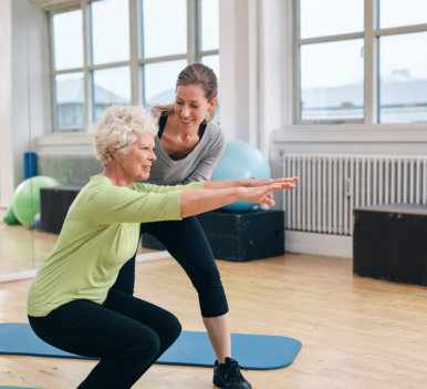 physical therapist assisting senior woman in exercising